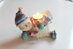 Cheerful snowman skier. Candlestick. Cheerful snowman skier. Candlestick with burning candle Royalty Free Stock Photo