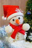 A cheerful snowman under the Christmas tree Royalty Free Stock Image