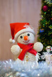 A cheerful snowman under the Christmas tree Royalty Free Stock Photos