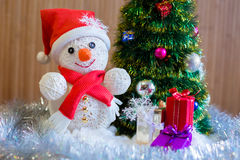 A cheerful snowman under the Christmas tree Stock Photography