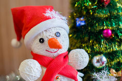 A cheerful snowman under the Christmas tree Royalty Free Stock Photo