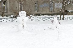 Cheerful snowmen from the snow stand in the courtyard of a house in the city and smile. stock image