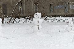 Cheerful snowmen from the snow stand in the courtyard of a house in the city and smile. royalty free stock photos