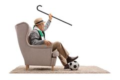 Cheerful soccer fan with cane and a scarf sitting in an armchair Stock Image