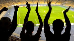 Cheerful soccer fans clapping at crowded stadium, supporting national sport team. Stock photo royalty free stock image