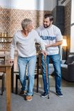 Cheerful social worker talking to a pensioner while helping him to walk. Kind volunteer. Positive kind reliable volunteer looking interested while talking to a Stock Images