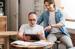 Cheerful son and dad. Loving son. Happy and smiling young men helping his cheerful father to use tablet being in a cafe Royalty Free Stock Photo