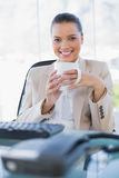 Cheerful sophisticated businesswoman holding coffee. In bright office royalty free stock photography