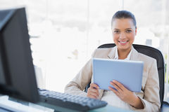Cheerful sophisticated businesswoman holding tablet pc. Cheerful sophisticated businesswoman in bright office holding tablet pc Royalty Free Stock Photo