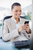Cheerful sophisticated businesswoman text messaging. In bright office Stock Photo