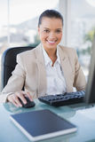 Cheerful sophisticated businesswoman working on computer. In bright office royalty free stock image