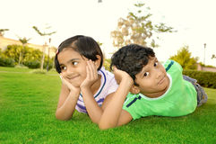 Cheerful south Asian boy and girl lying down in a lawn Royalty Free Stock Photography