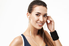 Cheerful sportive fitness girl in earphones smiling looking at camera over white background. Copy space Royalty Free Stock Photography