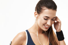 Cheerful sportive fitness girl in earphones smiling looking down over white background. Copy space Royalty Free Stock Photos