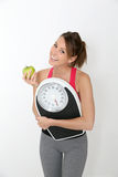 Cheerful sportive girl with green apple and scale Royalty Free Stock Images