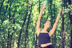 Cheerful sportive woman with water bottle in park royalty free stock image