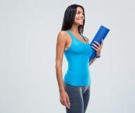 Cheerful sports woman holding yoga mat Stock Photo