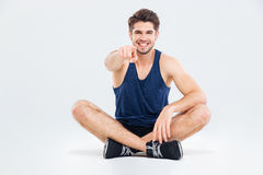 Cheerful sportsman sitting with legs crossed and pointing on you Stock Photos