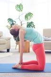 Cheerful sportswoman doing camel yoga posture Stock Photo