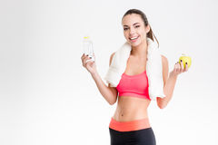 Cheerful sportswoman holding a bottle of water and an apple Royalty Free Stock Photography
