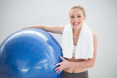 Cheerful sporty blonde with towel around her neck holding exercise ball Royalty Free Stock Photos