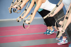 Cheerful sporty girls working with own weight. Close up of arms of young woman doing push-ups with trx equipment. They are stretching and leaning hands on straps stock photo