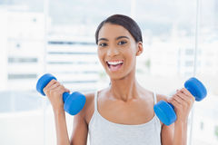 Cheerful sporty model exercising with dumbbells Royalty Free Stock Photography