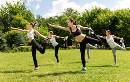 Cheerful sporty woman doing sport exercises. Activate your muscles. Pleasant delighted smiling women holding their legs and expressing positivity while doing Stock Photography
