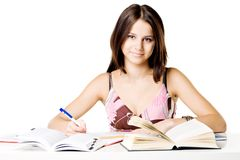 Cheerful student. Photo of a happy female student, doing homework Royalty Free Stock Photo