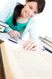 Cheerful student doing her homework on a desk Royalty Free Stock Image