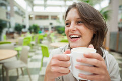 Cheerful student drinking coffee in the cafeteria Royalty Free Stock Photos