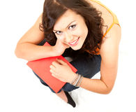 Cheerful student girl with book looking at camera Royalty Free Stock Photos