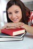 Cheerful student girl leaning on books stock photos
