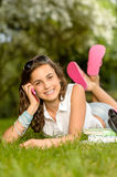 Cheerful student girl lying grass calling phone Royalty Free Stock Photos