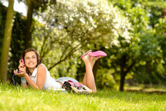 Cheerful student girl lying park listen music Stock Photo