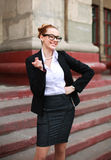 Cheerful student girl pointing a finger on university background Royalty Free Stock Photos