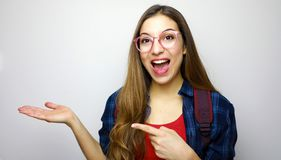 Cheerful student girl shows and pointing on white background a copy space stock image