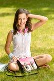 Cheerful student girl sitting on grass summer. Cheerful student girl with pink satchel sitting on grass summer Stock Photo