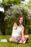 Cheerful student girl sitting grass thumb up Royalty Free Stock Image