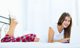 Cheerful student girl studing with laptop in bed Stock Image