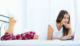 Cheerful student girl studing with laptop in bed Royalty Free Stock Photo