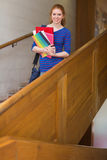 Cheerful student holding folders on the stairs looking at camera Stock Images