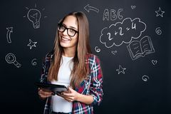 Cheerful student holding a modern device and looking interested stock images