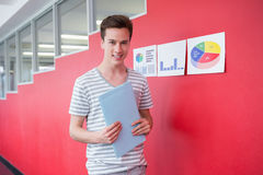 Cheerful student holding notebook standing. At the college Stock Photo