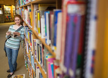 Cheerful student reading book leaning on shelf in library Royalty Free Stock Photos