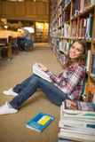 Cheerful student reading book on library floor Stock Images