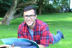 Cheerful student reading in the park.  Royalty Free Stock Photo