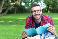 Cheerful student reading in the park.  Stock Photos