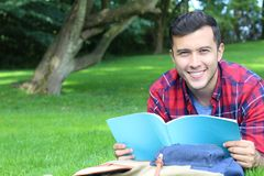 Cheerful student reading in the park.  Stock Images