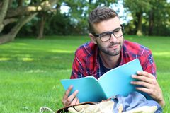 Cheerful student reading in the park.  Stock Photo